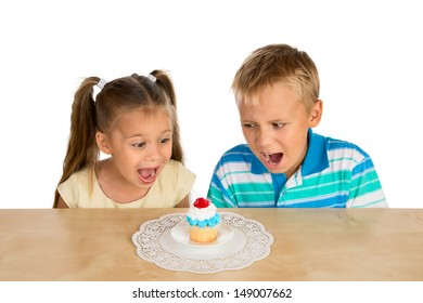 A girl and a boy are looking with excitement at a single delicious cupcake