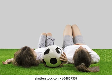 Girl and boy are lying on the grass with a soccer ball. Gray background