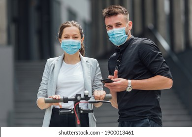 Girl and boy with medical mask  using smartphones to rent an e-kick vehicle. Couple with mobile phones using eco transport. Electric scooter  in urban background.