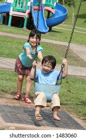 Girl & boy at the park swinging