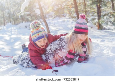 Girl and boy playing in big snow in winter. Happy caucasian child playing in snow forest