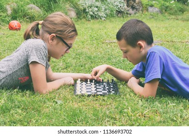 Girl and boy playing chess outdoors. Children lie on green grass in summer park. Happy childhood