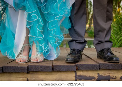 Girl and boy prom couple in formal suit and dress with focus on their feet in fancy shoes on wooden bridge