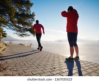 Girl and boy running while sun makes reflections in frozen lake surface. Regular sports activities do partners together