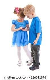 Girl and a boy are sending messages or are playing on his cell phones on white background. They dressed in blue.