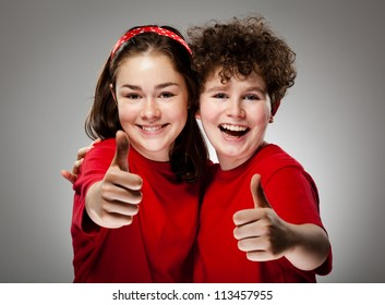 Girl and boy showing OK sign on gray background
