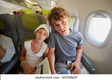 Girl and boy sit  in armchairs at airplane.