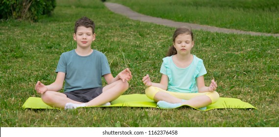 a girl and a boy sit on a yoga carpet and meditate, outdoors.