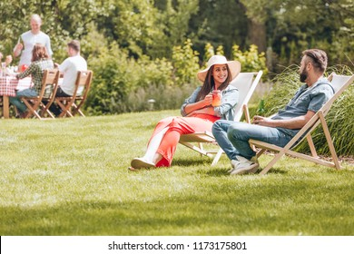 A girl and a boy sitting on deckchairs and flirting during afternoon yard party at a summer camp for students.