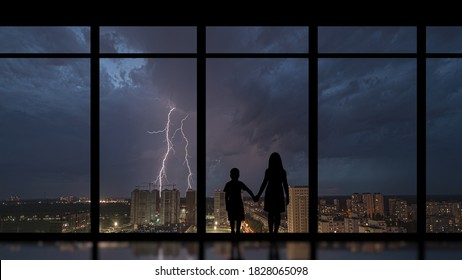The girl and boy standing near a panoramic window against the night lightning