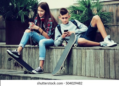 Girl and boy teens playing on mobile phones and listening to music outdoors