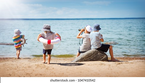 girl and boys standing on the beach in summer hats and holding steering wheel, lifebuoy and binoculars. Children playing at sea in nature