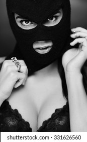 girl in bra and balaclava - black and white photo in studio of a psycho girl terrorist