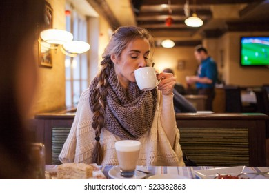 The girl with a braid and in a scarf sits in cafe. She has tea. Very cozy and warm photo. There is a wish to appear in the same place.