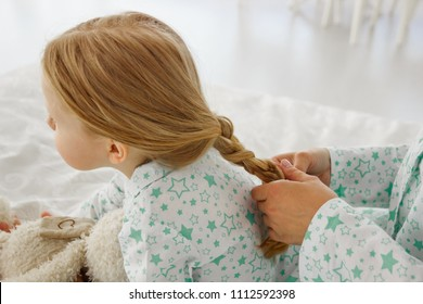 The girl is braided with a pigtail. Mom plaits a pigtail to her daughter. Make a haircut