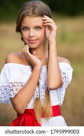 Girl with braided pigtails and red lace. Braids. Hairstyle