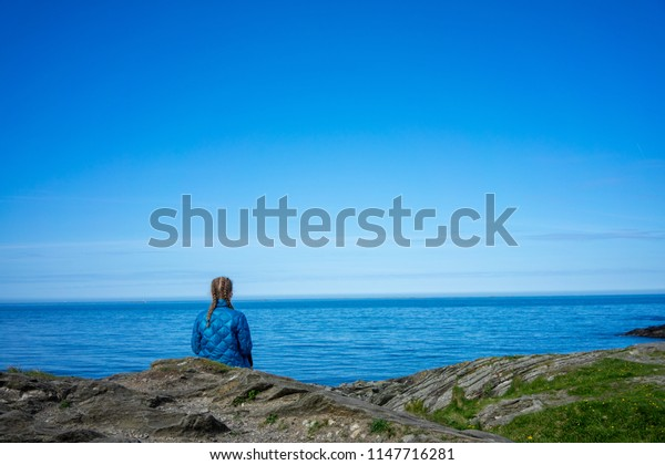 Girl with braids sits looking out to the sea, thinking about life.
