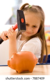 Girl breaking the piggy bank with hammer [focus on pig]
