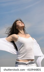 Girl breathes in fresh air on a blue sky background. She stands her arms to the side and her hair fluttering in the wind. Concept: freedom, health, cleanliness.