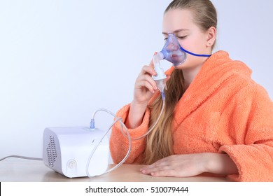 Girl breathing through a steam nebulizer. Treatment bronchopulmonary diseases. Isolated on white background