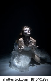 Girl Bride in Dead Man Skeleton Makeup Scares under Water. Halloween Concept