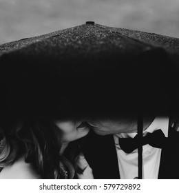 girl bride and groom in a black jacket and a butterfly kiss under a black umbrella on a rainy day, a black and white photo