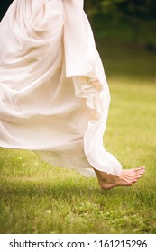 Girl bride running barefoot on the grass