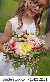 Girl bridesmaid holding small rustic seasonal September hand-tied wedding bouquet: pastel pink roses, dahlia, gypsophilia, astrantia, berries, foliage