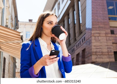 Girl in bright blue jacket stands with smartphone and coffee on the street