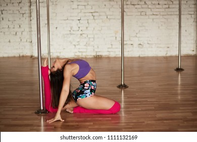 Girl in bright clothes does stretching and elements of pole dance in the gym
