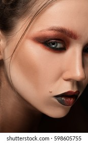 girl with bright make up. Glamour Portrait of beautiful woman model with red silver make up and romantic hairstyle. shiny brilliant Fashion highlighter on skin, sexy gloss lips and dark eyebrows.