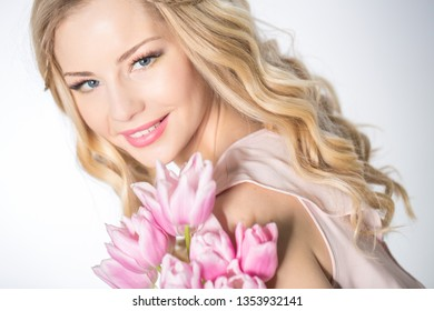 The girl with bright makeup holds a bouquet of pink tulips. Studio portrait. Spring bouquet in the hands of fragile blonde