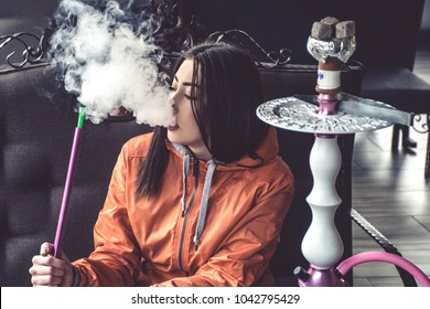 Girl in bright outfit smoking hookah