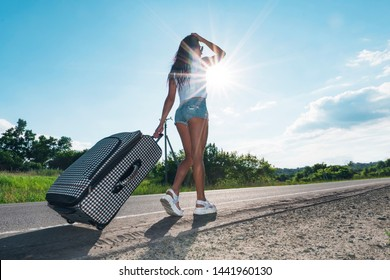 Girl in the bright sun on the road with Luggage on the background of the car. woman go on road with a suitcase. The concept of adventure and travel alone. Road trips. hitchhiking. Summer weekend.