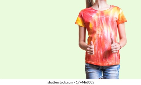 A girl in a bright t-shirt on a light background. White clothes painted by hand.