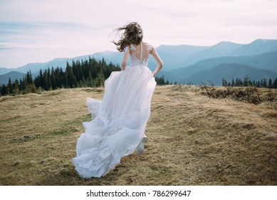 a girl in a bright wedding dress is running into the distance