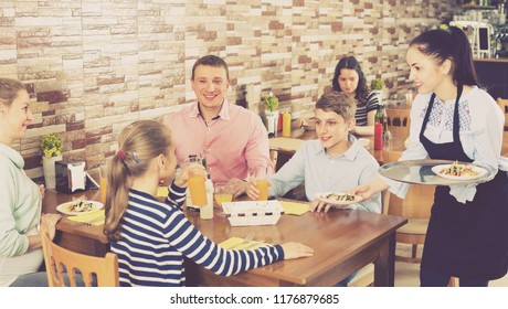 Girl is bringing salad and juice to young visitors of family cafe.