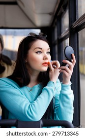 girl brings herself up, looks in the mirror, adjusts makeup in public transport, bus