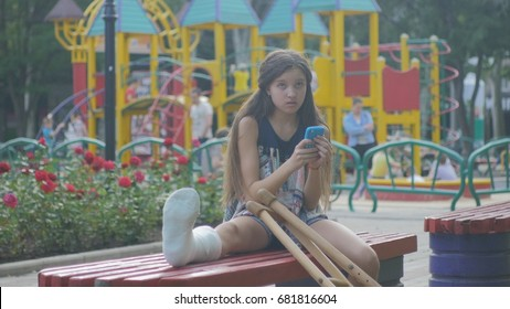 Girl with a broken leg sits on a bench, on the background of a descriptive pad and looks at the smartphone