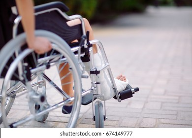 A girl with a broken leg sits in a wheelchair.