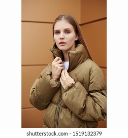Girl in a bronze down jacket on the street