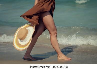 Girl in brown dress walking alongside beach, she holding bonnet hat in her hand. Close-up.