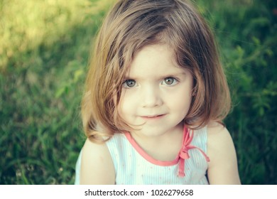 Girl with brown eyes on cute face sitting on green grass on sunny summer day. Childhood, leisure and fun. Innocence and youth concept.