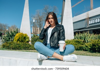 girl with brown eyes and a straight hair of brown color is very happy. Her fine features face are covered by the sun. She sits in earphones and enjoys music and the most fragrant coffee.