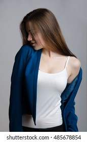 Girl with brown hair in blue jacket posing in studio on grey background