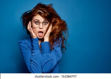 girl with brown hair in glasses on a blue background.