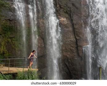 Girl with brown hair near waterfall