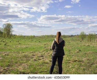 A girl with brown hair in a sport suit prepares for a run through the green summer field, a back view