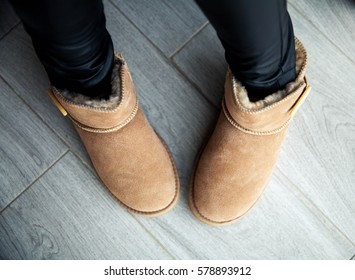 Girl in brown ugg boots in leather pants. Fashion, style, modern. Grey wood floor