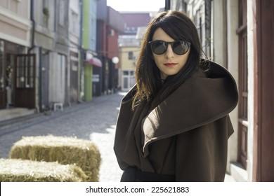 Girl in brown wool jacket on a street.